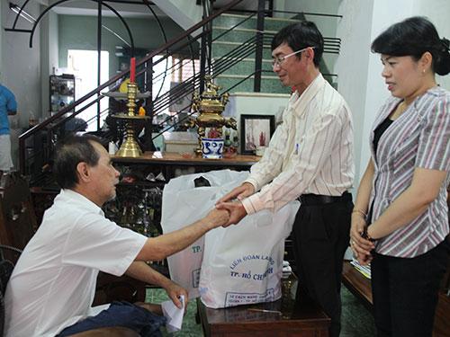 Ông Nguyễn Duy Vũ, Trưởng Phòng đoàn thể Ban Dân vận Thành ủy TP HCM (đứng), tặng quà cho công nhân bị tai nạn lao động