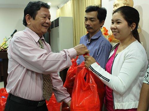 Ông Nguyễn Thanh Thắng - Chủ tịch LĐLĐ quận 4, TP HCM - tặng quà cho CNVC-LĐ có hoàn cảnh khó khăn Ảnh: BẢO NGHI