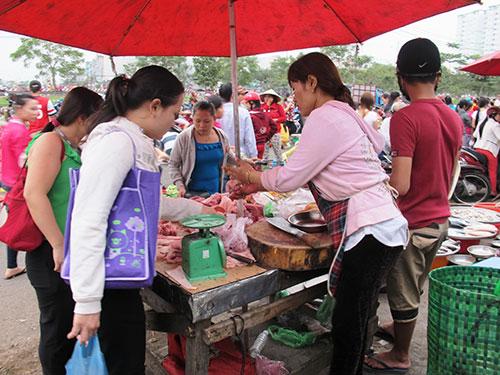 Thu nhập bấp bênh buộc công nhân phải dè sẻn trong chi tiêu. Trong ảnh: Công nhân Công ty Pou Yuen (quận Bình Tân, TP HCM) đang mua thực phẩm ở khu chợ tạm gần công ty Ảnh: HỒNG NHUNG