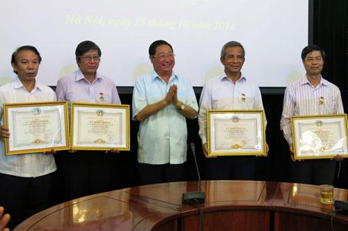 """Ông Giàng Seo Phử - Bộ trưởng, Chủ nhiệm Ủy ban Dân tộc (ở giữa) - trao kỷ niệm chương """"Vì sự nghiệp phát triển các dân tộc"""" cho các lãnh đạo Tổng LĐLĐ Việt Nam"""