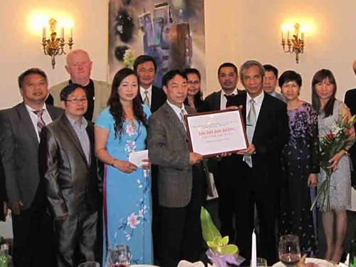 Chủ tịch Tổng LĐLĐ Việt Nam Đặng Ngọc Tùng (bìa phải) nhận tiền ủng hộ của kiều bào Việt Nam tại Cộng hòa Czech