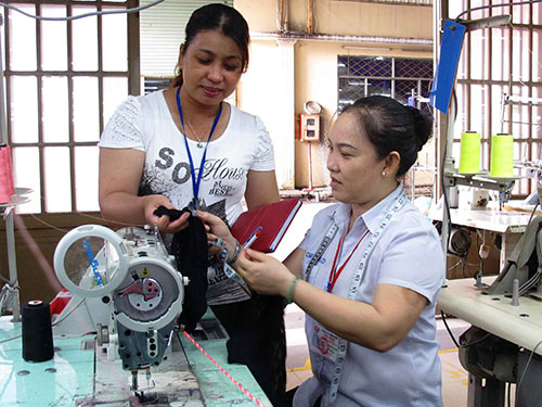 Chị Lê Thị Kim Dung (đứng) tận tình thăm hỏi, động viên công nhân trong quá trình sản xuất