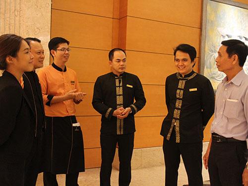 Anh Phạm Công Hầu (bìa phải) trò chuyện cùng nhân viên khách sạn Equatorial