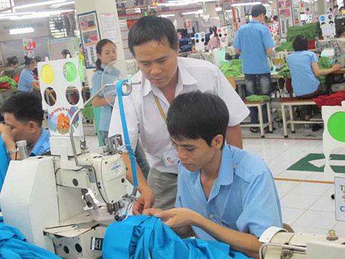 Anh Trần Văn Dương hướng dẫn kỹ thuật cho công nhân tại xưởng may