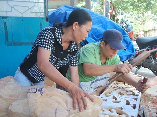Chị Nghệ đang hướng dẫn thợ thực hiện một sản phẩm điêu khắc