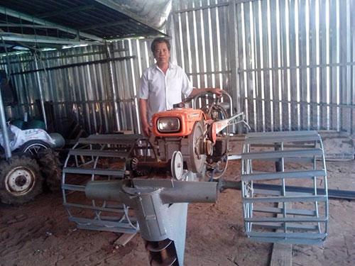Ông Cao Văn Tám bên một chiếc máy vét bùn đang được hoàn thiện