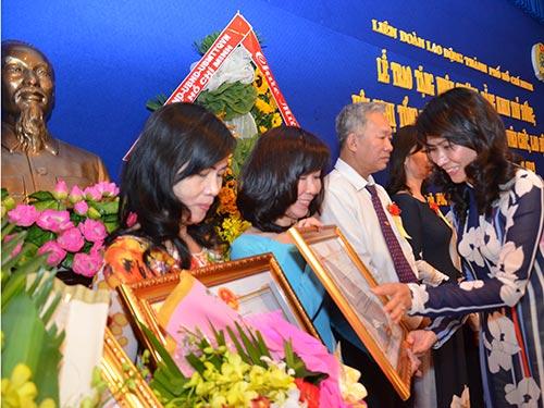 Bà Nguyễn Thị Thu, Chủ tịch LĐLĐ TP HCM, tặng bằng khen cho các tập thể, cá nhân tiêu biểu Ảnh: TẤN THẠNH