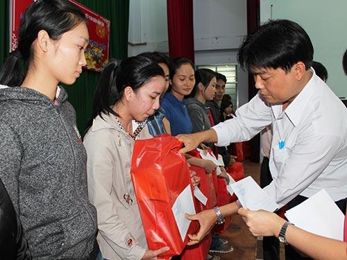 Ông Nguyễn Văn Hải, Phó Chủ tịch LĐLĐ quận Bình Tân, TP HCM, tặng quà cho công nhân mất việc Ảnh: THANH NGA