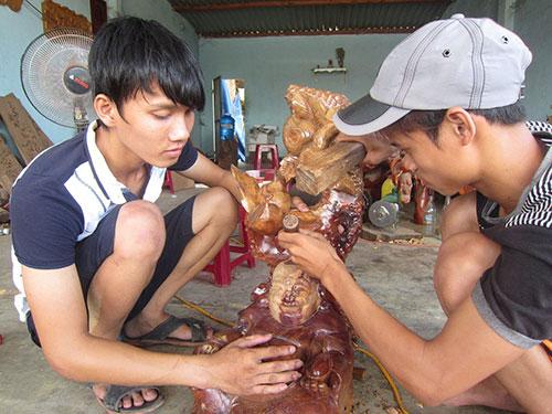 Nguyễn Ngọc Hiệp (trái) luôn hướng dẫn tận tình cho những bạn trẻ khi họ đến học nghề tại cơ sở điêu khắc gỗ Lạc Việt