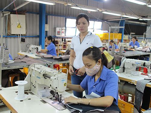 Chị Trần Ngọc Sậm hướng dẫn công nhân tổ may sofa may mẫu