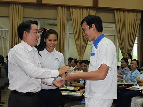 Ông Kiều Ngọc Vũ (trái), Phó Chủ tịch LĐLĐ TP HCM, tặng thiệp chúc Tết cho cán bộ Công đoàn khu vực  Tân Thuận Ảnh: THANH NGA