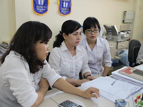 Chị Nguyễn Thị Ngọc Thúy, nhân viên kinh doanh Xí nghiệp In Bến Thành (giữa), trao đổi kế hoạch công tác với đồng nghiệp