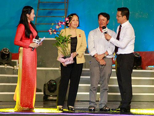 """Bác sĩ Phan Kim Phương, Giám đốc Viện Tim TP HCM (thứ hai từ trái qua), nhận hoa của một công nhân được mổ tim trong chương trình """"Trái tim nghĩa tình"""" Ảnh: HOÀNG TRIỀU"""