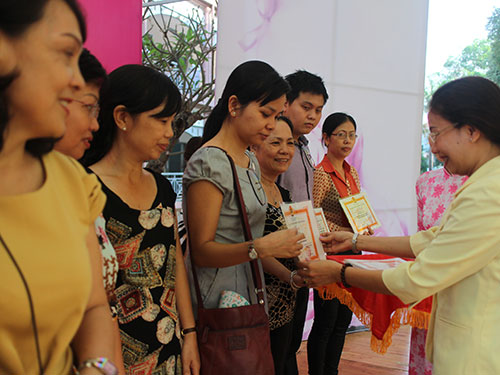 """Bà Huỳnh Thị Ngọc Liên, Trưởng Ban Nữ công LĐLĐ TP HCM, trao giấy khen cho các CĐ cơ sở tích cực trong phong trào """"Nuôi heo đất"""""""
