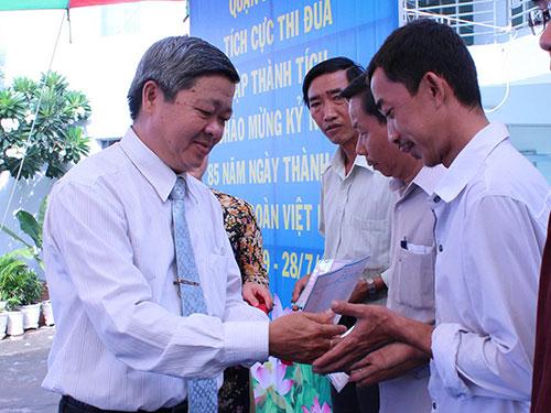 Ông Nguyễn Văn Dễ - Chủ tịch LĐLĐ quận Bình Tân, TP HCM - trao sổ tiết kiệm cho công nhân khó khăn