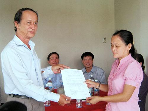 Đại diện CĐ Giáo dục TP (trái) trao quyết định tặng nhà cho giáo viên có hoàn cảnh đặc biệt khó khăn
