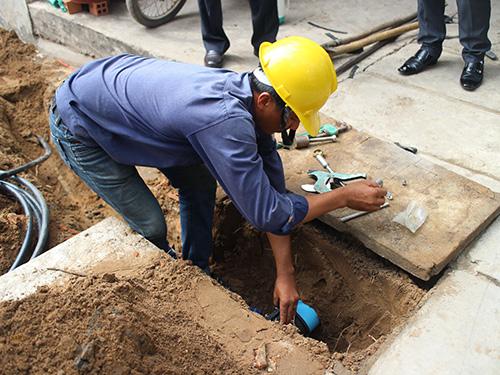 Công nhân Công ty CP Cấp nước Nhà Bè gắn đồng hồ nước cho hộ bà Bùi Thị Gia