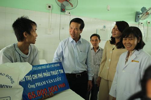 Ông Võ Văn Thưởng trao tiền hỗ trợ cho anh Phạm Văn Luốt (bìa trái)