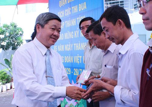 Ông Nguyễn Văn Dễ - Chủ tịch LĐLĐ quận Bình Tân, TP HCM - trao sổ tiết kiệm cho công nhân Ảnh: THANH NGA