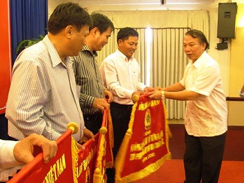 Ông Mai Đức Chính, Phó Chủ tịch Tổng LĐLĐ Việt Nam, trao cờ thi đua cho các đơn vị