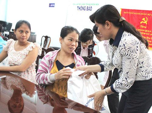 Bà Nguyễn Trần Phượng Trân, Phó Chủ tịch LĐLĐ TP HCM (bìa phải), tặng quà cho công nhân Công ty Kiên Tường