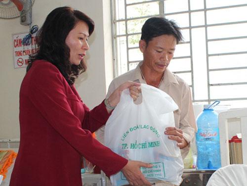 Bà Nguyễn Thị Thu, Chủ tịch LĐLĐ TP HCM trao quà cho người nhà công nhân bị bỏng