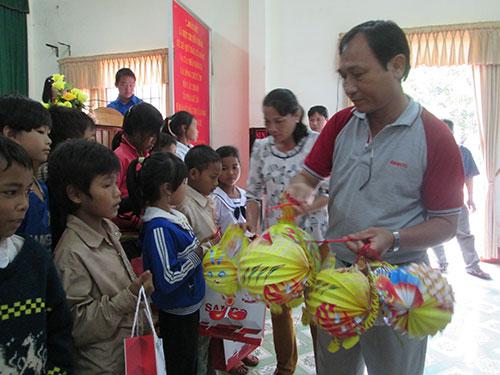 Ông Nguyễn Châu Nghĩa, Chủ tịch CĐ SAMCO, tặng lồng đèn cho học sinh nghèo tại xã Lộc An, huyện Lộc Ninh, tỉnh Bình Phước Ảnh: KIM NGÂN