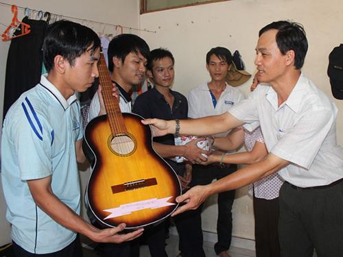 Cán bộ chuyên trách LĐLĐ quận Phú Nhuận (phải) tặng sách và đàn guitar cho CN ở trọ Ảnh: THANH NGA