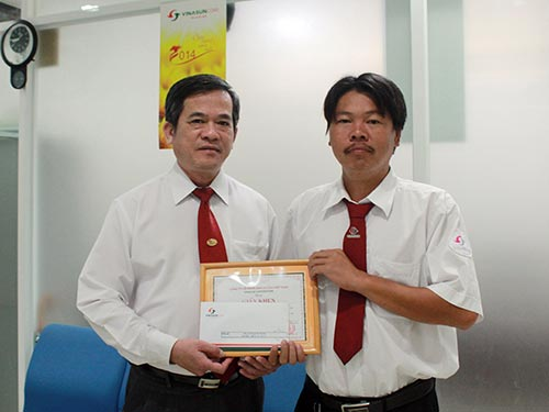 Ông Huỳnh Văn Sỹ, Phó Tổng Giám đốc Vinasun (bìa trái), trao giấy khen và tiền thưởng cho tài xế Ninh Quốc Hùng