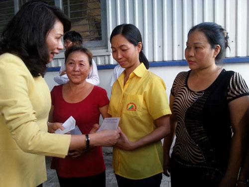Bà Nguyễn Thị Thu, Chủ tịch LĐLĐ TP HCM, trao tiền hỗ trợ cho công nhân