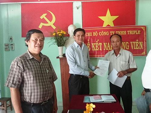 Ông Lê Trần Thanh Hải (giữa) nhận quyết định kết nạp đảng viên