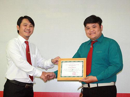 Ông Đặng Thành Duy, Phó Tổng Giám đốc Vinasun (bên trái), trao giấy khen cho anh Phạm Văn Quí