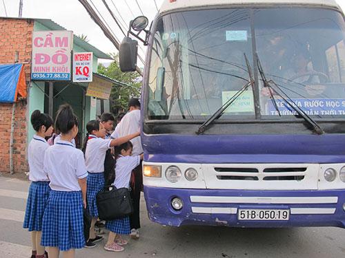 Học sinh ở huyện Hóc Môn, TP HCM chờ xe đưa rước đến trường Ảnh: THU HỒNG