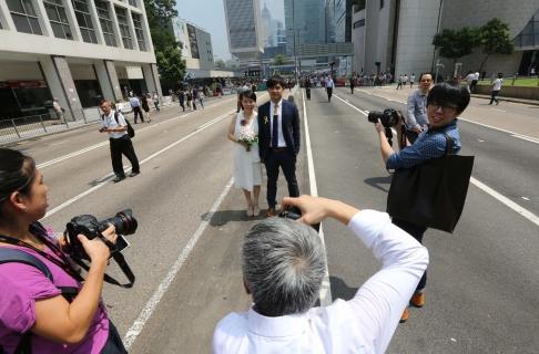 Một cặp đôi tranh thủ chụp hình cưới, đằng sau là những người biểu tình. Ảnh: SCMP