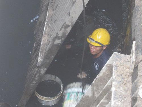 Một công nhân chui xuống cống nước ngập ngang ngực để nạo vét bùn Ảnh: Lương Sơn