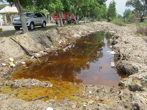 """Đắp đê đất """"nhốt"""" hóa chất khỏi lan ra xa. Gần 1 tháng xảy ra sự cố cháy, nước kênh 6 vẫn còn nhuộm màu nâu đỏ của hóa chất"""