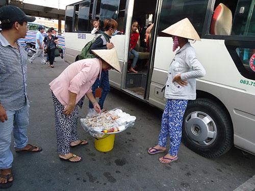 Hàng rong ở Bến xe Miền Tây đến từng xe mời mọc khách Ảnh: Nguyễn Phượng