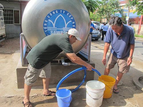 Nhiều người dân ở quận 12, TP HCM phải sử dụng nước sạch thông qua bồn chứa do SAWACO cung cấp Ảnh: THU HỒNG