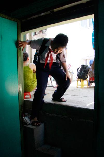 Một em nhỏ phải khom người để chui vào nhà mình ở hẻm 1007 Lò Gốm, quận 6, TP HCM Ảnh: HOÀNG TRIỀU