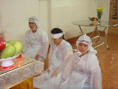 Bà Dương Thị Thảo cùng 2 con thắp hương chuẩn bị cúng cơm cho chồng, cha là ông Nguyễn Văn Chín và bút tích của ông Chín (ảnh nhỏ)