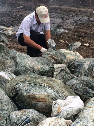 Những bao chứa chất thải màu xanh nghi là bùn công nghiệp được Thanh tra Sở TN-MT lấy mẫu sáng 18-7 Ảnh: THU HỒNG