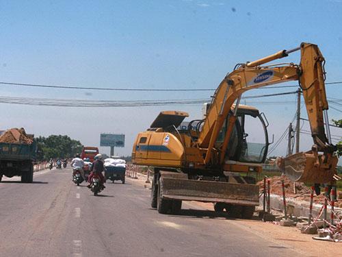 Các phương tiện phục vụ cho việc thi công Quốc lộ 1 qua địa phận tỉnh Quảng Nam đậu ngổn ngang gây khó khăn cho người tham gia giao thông Ảnh: QUANG VINH