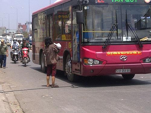 """Giữa trưa nắng gắt, người phụ nữ này vẫn bế đứa trẻ ngồi giữa giao lộ xin ăn. Khi có xe buýt đến, cô ta đứng dậy tránh rồi lại tiếp tục """"hành nghề"""""""