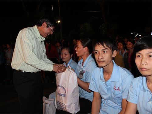 Ông Trần Thanh Hải và bà Nguyễn Thị Thu cùng trao những tấm vé xe tặng công nhân về quê đón TếtẢnh: THANH NGA