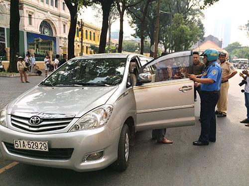 Thanh tra giao thông lập biên bản xử phạt hành chính một xe Uber