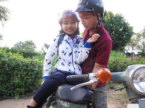 Võ Văn Huy đưa đón người em út bị tật nguyền đến trường