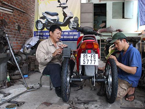 Ông Võ Đình Minh (trái) lắp ráp xe cho khách hàng