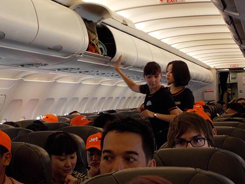 Tiếp viên kiểm tra lại giá để hành lý của khách trước khi máy bay cất cánh Ảnh: PHƯƠNG ANH