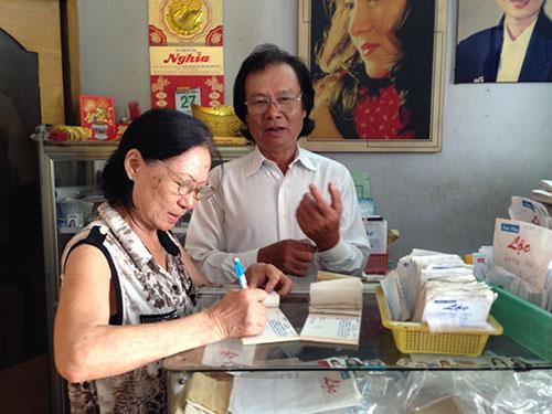 Vợ chồng ông Lộc bận rộn chọn ảnh cho những khách hàng quen thuộc