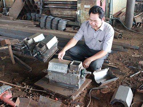 """Anh Đặng Văn Bẩy bên chiếc máy phân loại cà phê mang tên """"Thành công mới"""""""